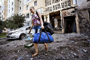A woman walks out of a damaged Donetsk multi-storey block of flats carrying her belongings.