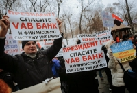 People hold a placards reading 'President save VAB bank and financial system in Ukraine' during a rally against the financial policy of the Ukrainian National Bank in front of the Cabinet of Ministers building in downtown Kiev, Ukraine, 16 December 2014.