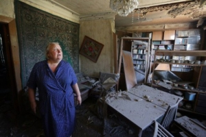 A woman assesses the damages to her house as a result of shelling between Ukrainian forces and pro-Russian separatists in the eastern Ukrainian city of Donetsk on July 19, 2015. Russian Foreign Minister Sergei Lavrov held separate talks on July 18 with his Ukraine, US and German counterparts, the Kremlin announced, as fighting spikes in eastern Ukraine. AFP PHOTO/ ALEKSEY FILIPPOV