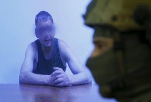 An officer of the Security Service of Ukraine (SBU) stands next to a monitor showing a man, who according to SBU is a Russian army major detained by Ukrainian servicemen at the weekend, during a news briefing in Kiev, Ukraine, July 29, 2015.