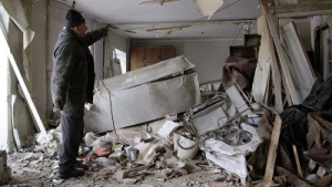 A Ukrainian man shows his building which was damaged during clashes between Ukrainian security forces and pro-Russian separatists in Donetsk, Ukraine, on Jan. 15, 2015.