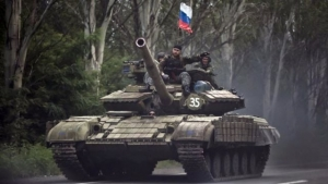 Pro-Russian rebels ride on a Russian tank flying Russia's flag on a road east of Donetsk, eastern Ukraine.