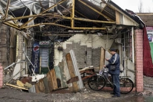 A man checks his mobile phone in front of his destroyed house in the town of Debaltseve, north-east from Donetsk, March 13, 2015.