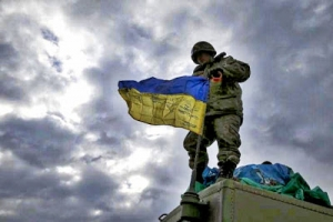 A Ukrainian serviceman who fought in Debaltseve hoists a Ukrainian national flag before leaving for home, near Artemivsk.