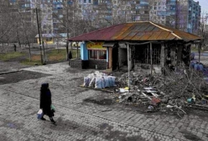 A woman walks past a burnt-out a store at a residential sector affected by shelling in Mariupol, a city on the Sea of Azov, eastern Ukraine.