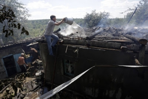 Residents of the eastern Ukrainian town of Avdiivka, in the Donetsk region controlled by Ukrainian forces, extinguish a fire on their house during shelling by pro-Russian separatists on Wednesday.