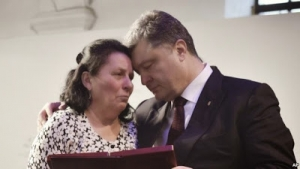 Ukrainian President Petro Poroshenko, right, presents a Hero of Ukraine award to a relative of an activist killed a year ago during mass protests, at the award ceremony in Kiev, Feb. 20, 2015.