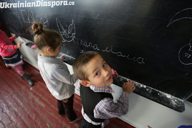 Children write on the blackboard at a school in the village of Staromykhailovka, which is on the frontline between the cities of Donetsk and Mariyanovka, Ukraine.
