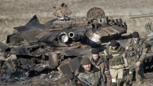 Russia-backed separatists walk after inspecting destroyed Ukrainian army tanks for functional weapons and ammunition near the village of Lohvynove, outside Debaltseve, Ukraine, Sunday, Feb. 22, 2015, on the edge of the territory under their control.