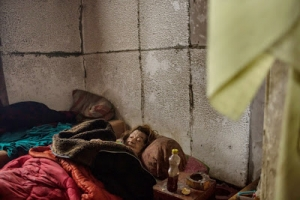Lyuba Sklyarova lays on a mattress on the floor beneath layers of soiled blankets.