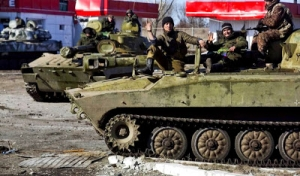 Pro-Russian fighters with the separatist self-proclaimed Donetsk People's Republic army sit on top of mobile artillery units in the town of Debaltseve February 22, 2015.