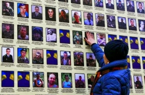 A woman touches a portrait of her husband in Kiev, on a banner with portraits of Ukrainian servicemen killed in the conflict with pro-Russian separatists in eastern Ukraine, November 25, 2014.