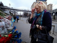 "Elena Bilan, 55, prays at a makeshift shrine in Kiev to dozens of people killed by mysterious snipers during last year's Maidan uprising that resulted in the ousting of former president Viktor Yanukovych. ""What will happen next year I don't know. I have a son at the front and I help him with everything I have,"" Bilan said."