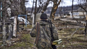 A pro-Russian rebel walks along their position at the frontline in a village not far form Luhansk, eastern Ukraine, Thursday, March 12, 2015.