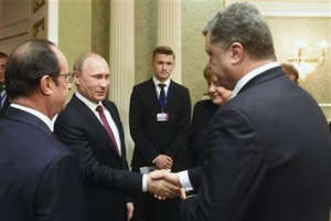 Russian President Vladimir Putin, second left, and Ukrainian President Petro Poroshenko, right, shake hands as French President Francois Hollande, left, and German Chancellor Angela Merkel look on during a meeting in Minsk, Belarus, Wednesday, Feb. 11, 2015. Leaders of Russia, Ukraine, France and Germany are gathering for crucial talks in the hope of negotiating an end fighting between Russia-backed separatist and government forces in eastern Ukraine. (AP Photo/BelTA, Andrei Stasevich)